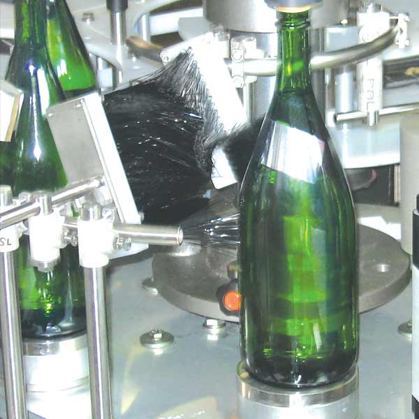 A green bottle getting ready for a label and shrink wrap.