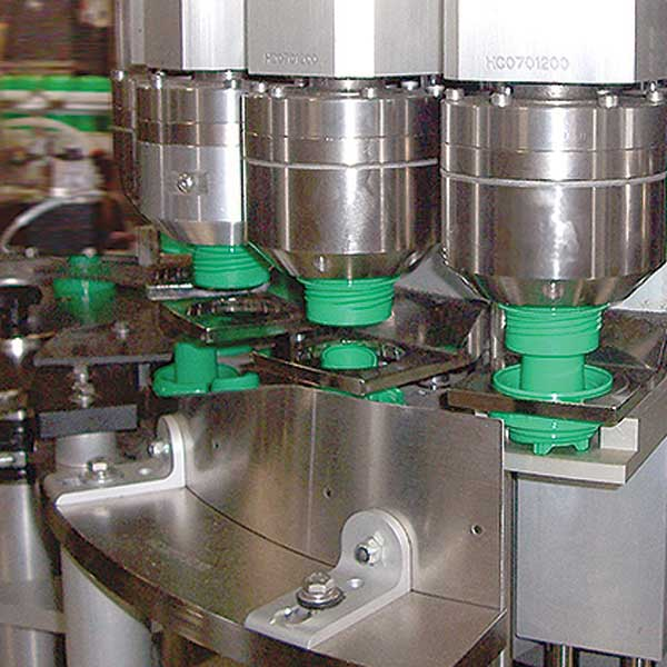 A collection of a plastic deodorant spout control being assembled in a machine.