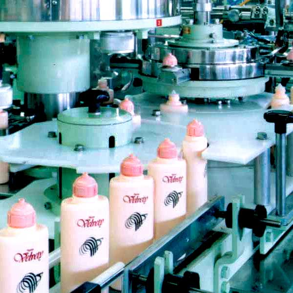 A line of lotion products in an assembly line.