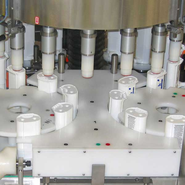 A collection of yogurt containers in an assembly line.