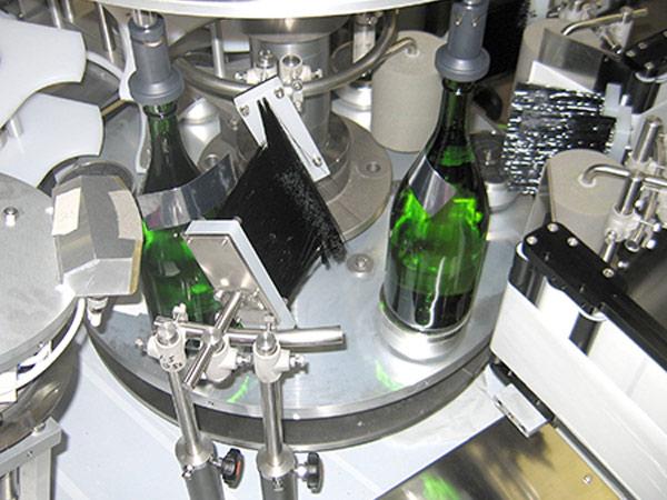 A green glass bottle receiving a label.