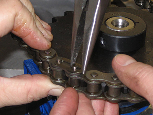 A technician installing a chain around a gear.