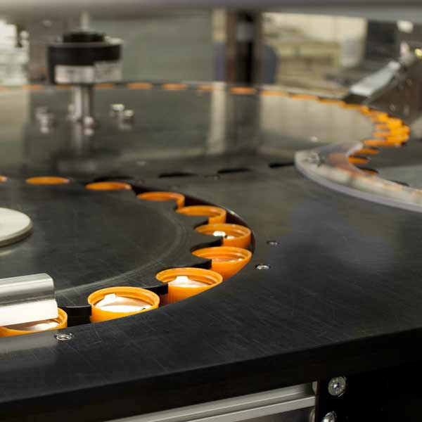 A line of orange plastic tops being processed.