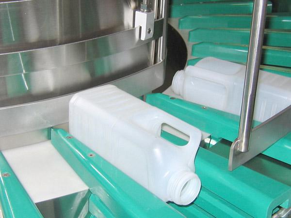 A plastic milk jug on a conveyer in a machine.